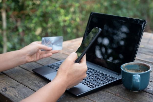 ラップトップと木製テーブル上のコーヒーと一緒にスマートフォンとクレジットカード。