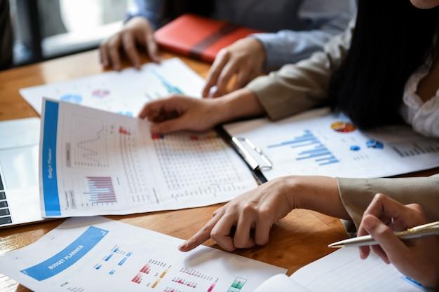 ガールオフィスチームは机の上のグラフを分析しています。