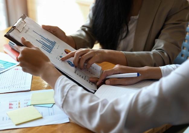 女性会社員保持ファイル。彼らはグラフを分析しています。
