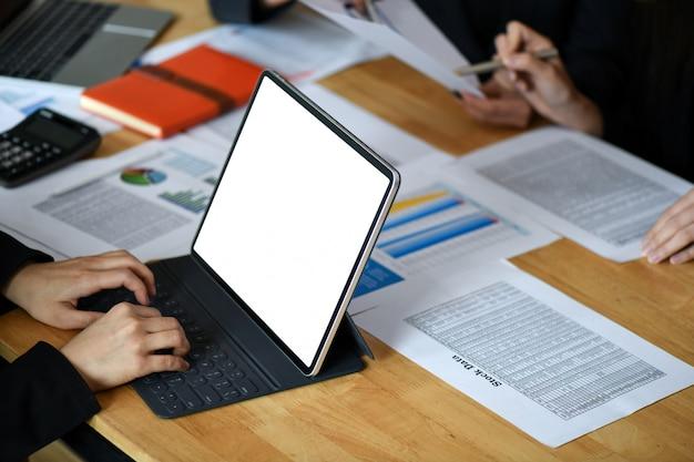 実業家は、机の上のグラフとチャートで空白のタブレットコンピューターの画面に取り組んでいます。