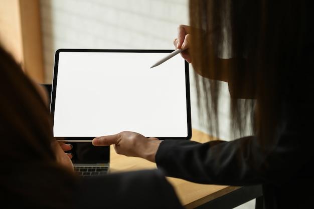 チーム実業家のオフィスで空白の画面現代タブレットに取り組んでいます。