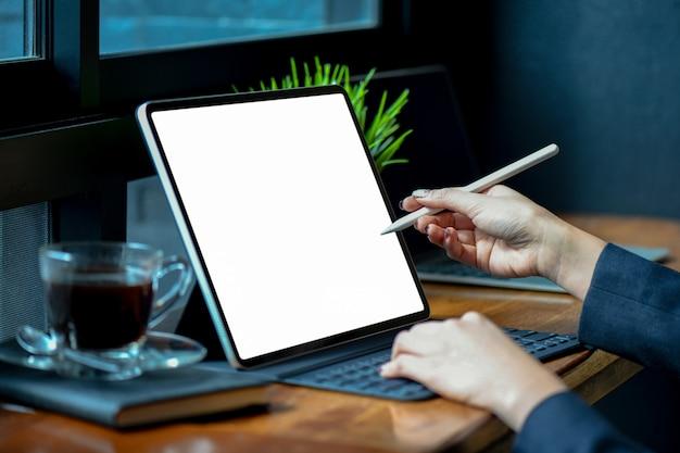 実業家のオフィスで空白の画面現代タブレットに取り組んでいます。