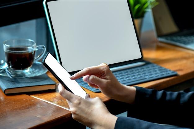 実業家は、空白の画面のスマートフォンで近代的なタブレットのオフィスで作業します。