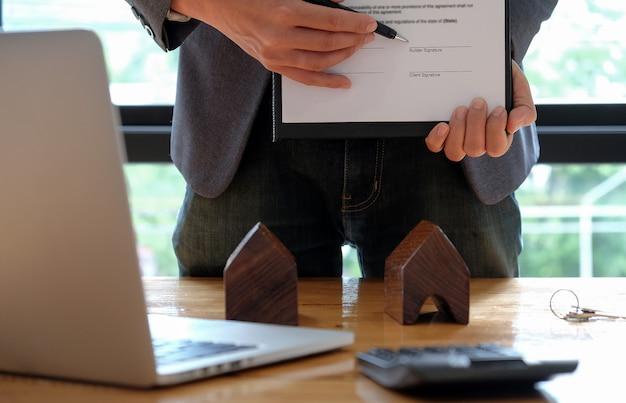 Бизнесмены продают дом, указывая на подписание договора купли-продажи в офисе.