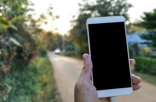 携帯電話空白の黒い画面を保持している女性のモックアップ画像。