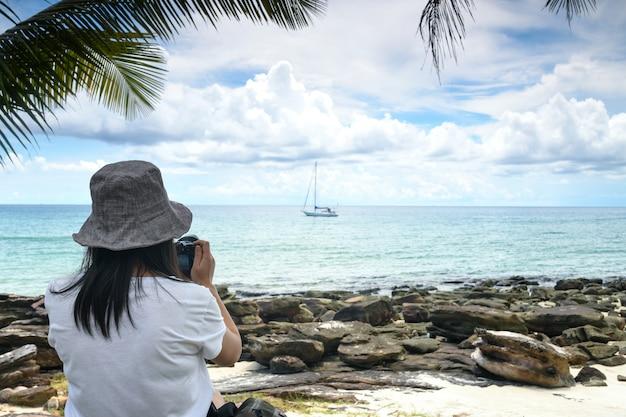 女性観光客がビーチで写真を撮っています。