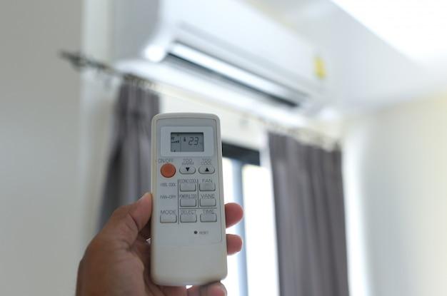 人々はリモコンのエアコンを使用しています。