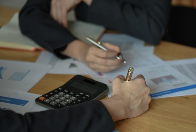 Женский бухгалтер команда анализирует данные, чтобы подвести итоги бюджета.