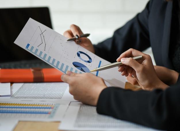 ビジネスコンセプトを立ち上げ、新しいオフィスのスタッフはグラフからデータを分析しています。