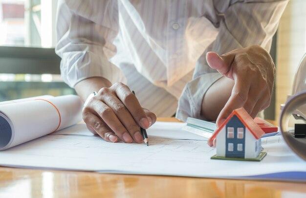 ハウスデザイナーは、家のデザインをチェックして顧客に提供しています。