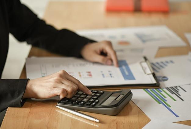 女性ビジネスマンは電卓、ペンを使用して、品質を改善するためのマーケティング計画を計画します。