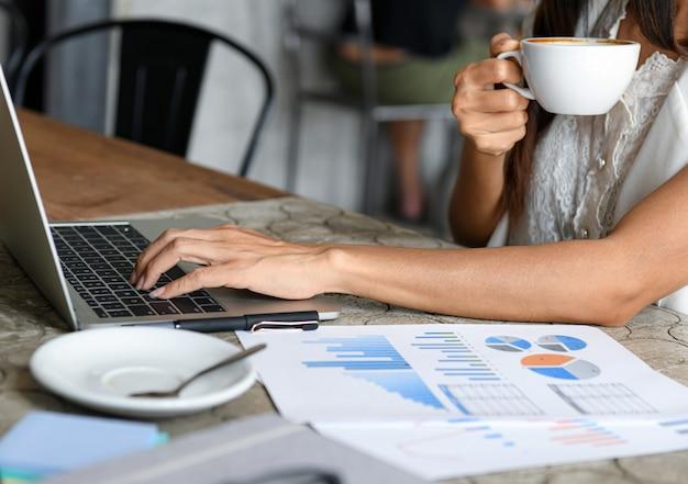 女性ビジネスマンはコーヒーを食べて、ラップトップを使用しています。