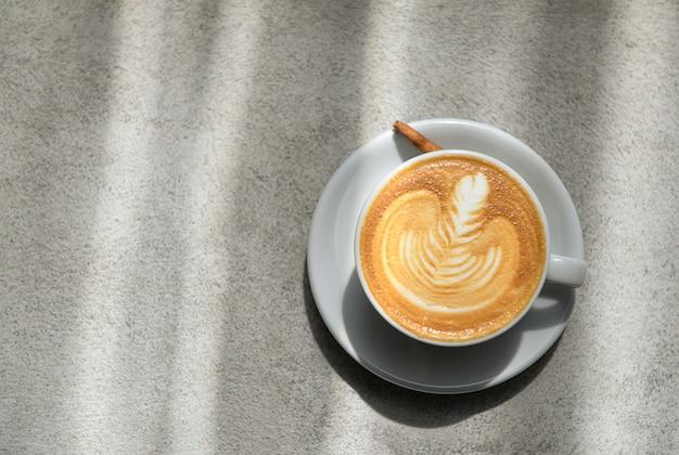 コンクリートの床に置かれた葉の上に描かれたラテコーヒー。