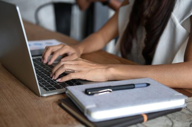 幹部はラップトップを使用しています。彼女はキーボードに手を置いた。前面には、テーブルにノートとペンが置かれています。