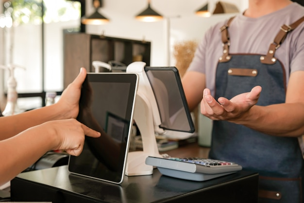 バリスタは、画面を使用して顧客からの注文を受け付けています。