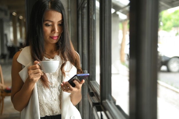 コーヒーカップを手に保持している白いドレスを着たアジアの女性は、携帯電話を使用しています。