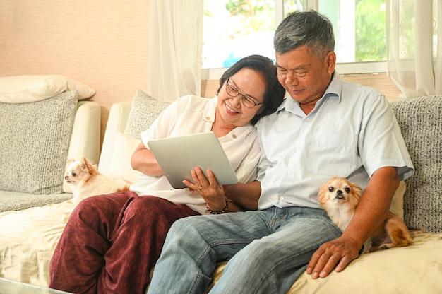 Пожилая женщина и азиатский человек сидя на софе используют таблетку.