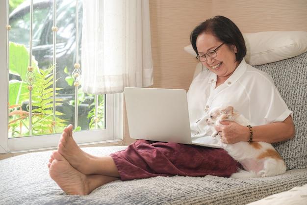 Пожилая азиатская женщина сидя на софе использует компьтер-книжку. она счастливо улыбнулась, собака чихуахуа села на бок.