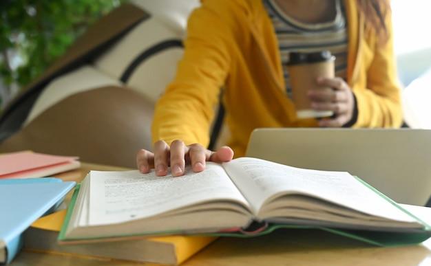 学生は本を読んで、試験の準備のためにメモを取っています。