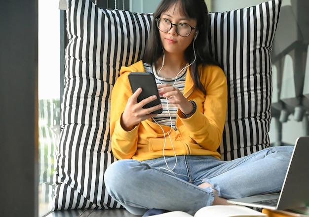アジアの女子学生が眼鏡をかけて、スマートフォンやヘッドフォンから音楽を聴きます。