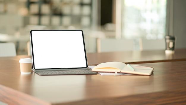 Портативный компьютер пустого экрана и кофе в современном офисе с тетрадью.