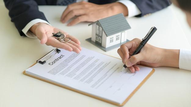 Концепция недвижимости, клиент подписывает контракт о договоре ипотечного кредита.