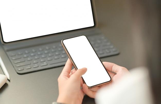 実業家の手の画像を閉じるには、ノートパソコンで空白の画面のスマートフォンを使用しています。