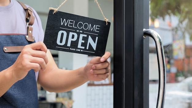Владелец бизнеса держит открытый знак для предоставления услуг