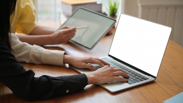 教師は自宅で生徒にオンラインで教えるためのラップトップを準備しています