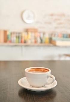 木製のテーブルに白いコーヒーのマグカップ