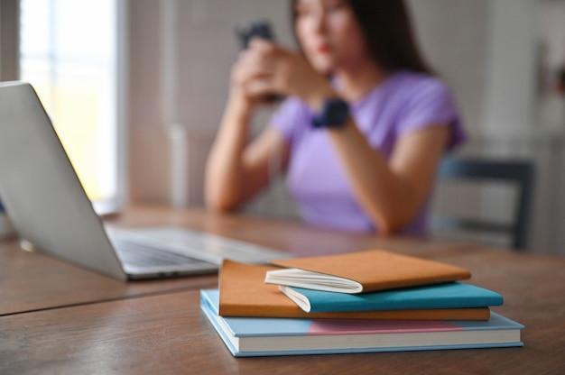 テーブルの上にラップトップがあり、背中にスマートフォンを使用している若い女性のノート