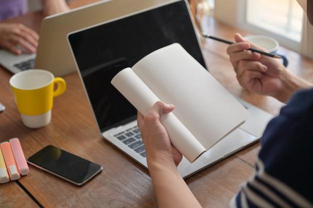 Студенты делают записи в тетради. они учатся онлайн с ноутбуком дома.