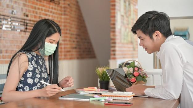 Женщина в маске и молодой человек в поисках информации от ноутбука и планшета