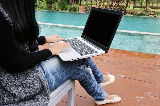 Предприниматель, очаровательная красивая загорелая кожа азиатский бизнес шикарная женщина ручной работы на ноутбуке у бассейна