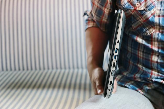 男は腕とソファコピースペースでラップトップを保持します。