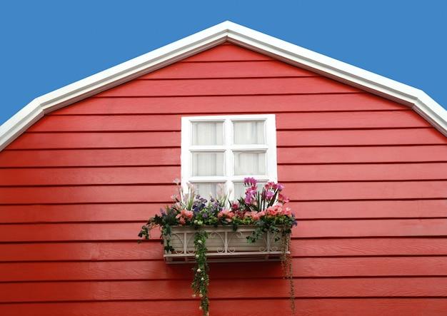 赤い納屋の上に花と白いウィンドウ