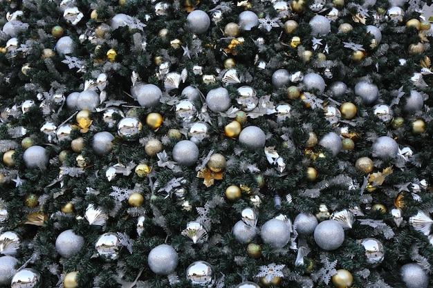 ゴールドカラーのクリスマスボールは緑の松の木にハングします。