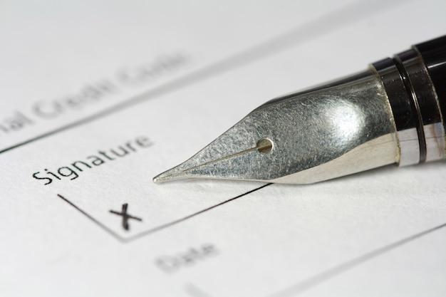 署名紙の上の金属の万年筆
