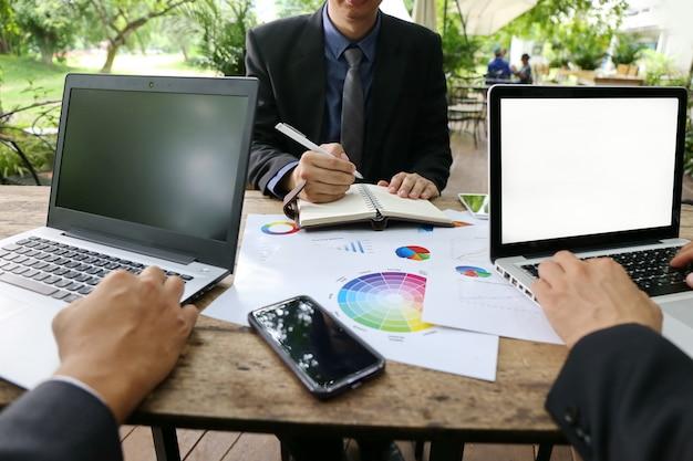 さまざまな国籍の人々のグループは、現代のオフィスでラップトップで働く成功を喜んで元気です。