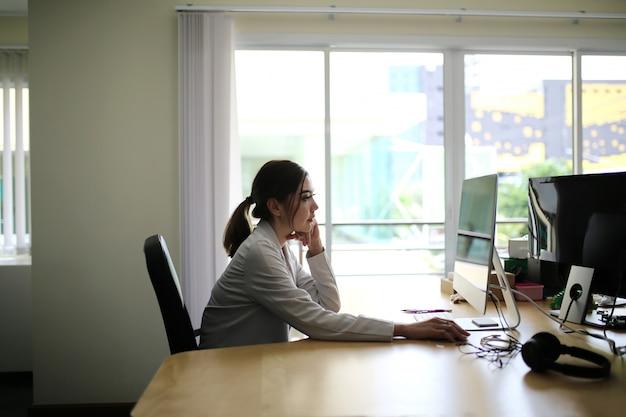 魅力的な美しい日焼け肌アジアシックなスマートな女性手ラップトップ電話で作業します。