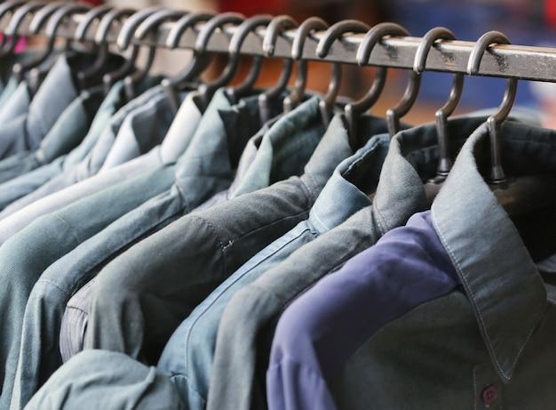 Синяя рубашка магазин, через новую одежду во время покупок
