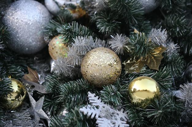 ゴールドカラーのクリスマスボールは、ぼやけた夜の光新年パーティーで緑の松の木にハング