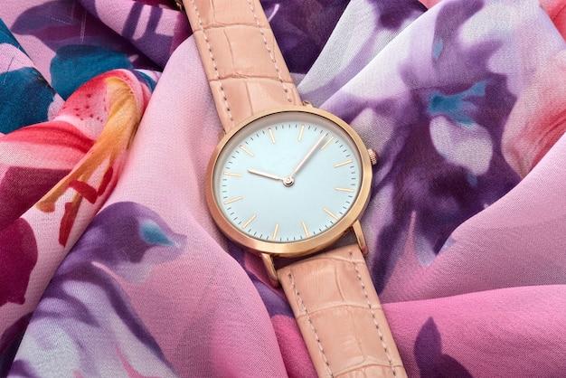 カラフルなシルクファブリックの背景にピンクの腕時計