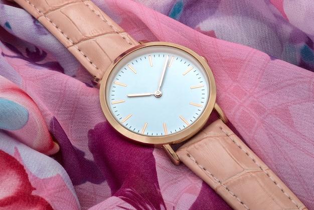 カラフルなシルクファブリックの背景に腕時計