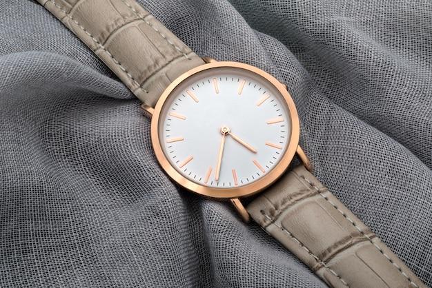 灰色のシルクファブリックの背景に腕時計