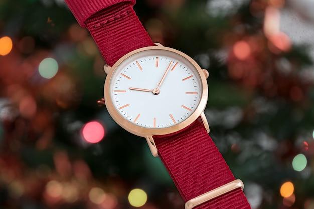 クリスマスライトの前に赤いナイロンストラップの腕時計