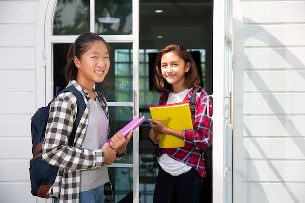 Две подростковые азиатские и европейские студентки подружки с удовольствием идут в колледж или школу