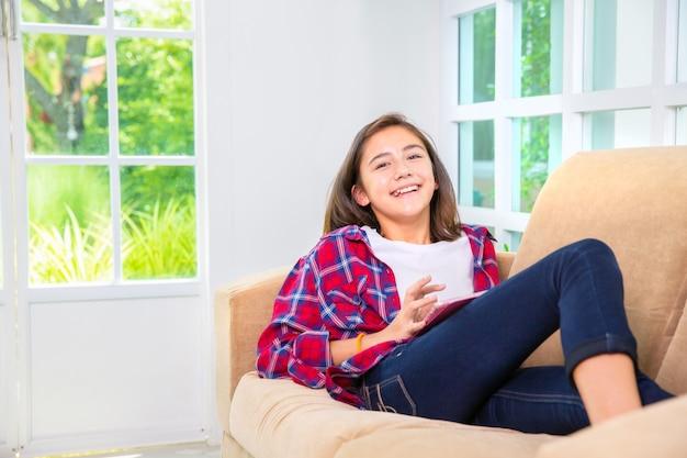 Кавказская девушка играет смартфон или планшетный пк на диване у себя дома