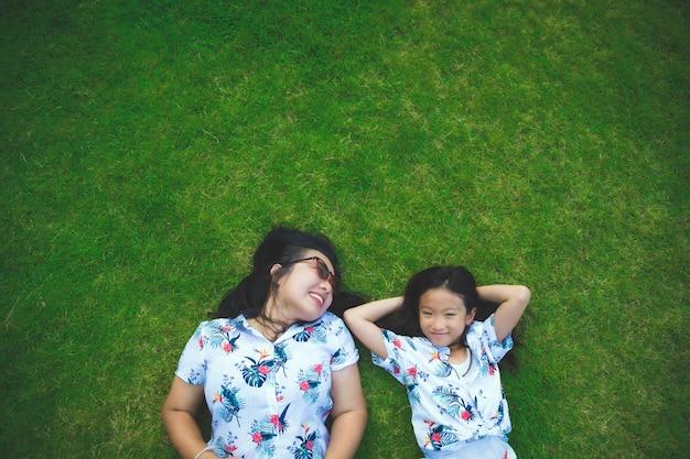 Мама и дочь счастливы, лежа на траве