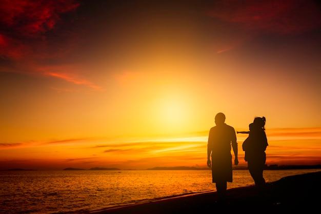 日の出や日没のビーチで幸せなシルエット家族。自由な生活と幸福の概念
